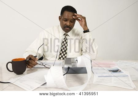 Tensed African American accountant with expense receipt and documents at office
