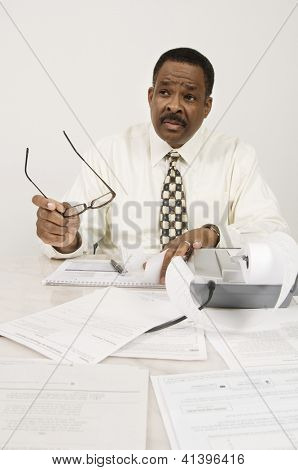 An African American financial adviser communicating with someone while holding glasses in office