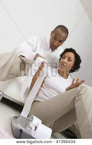 Worried African American couple looking at expense receipt