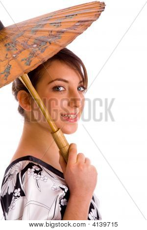 Side View Of Smiling Chineese Woman Holding An Umbrella