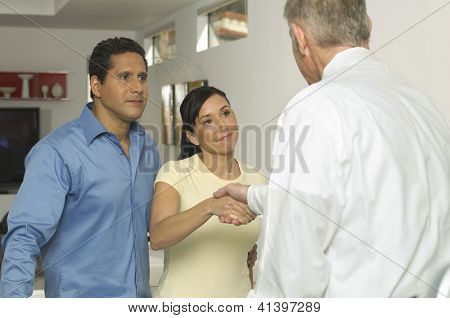 Happy couple seal a deal with their personal financial adviser at home