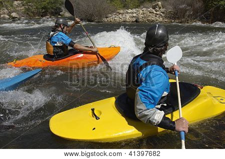 Caucasian teammates river rafting together