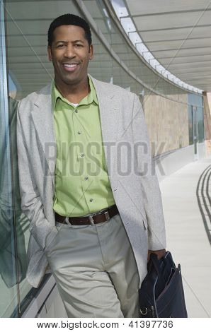 Portrait of an African American man with briefcase leaning on glass