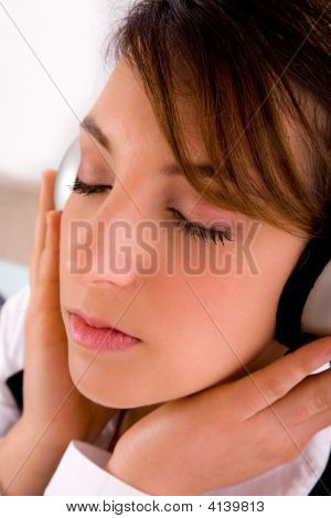 Side View Of Female Professional Listening To Music