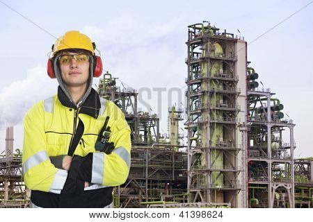 Young chemical engineer posing in front of a biodiesel refinary plant, wearing a hard hat, fire retardant clothing with reflective stripes, looking proudly into the camera