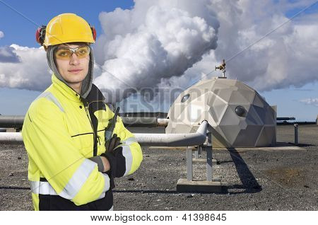 Engineer, wearing all necessary safety gear, standing in front of a futuristic dome, a part of a geothermal and sustainable energy plant in Iceland