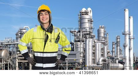 Proud and confident chemical engineer smiling into the camera in front of a petrochemical plabnt, with stainless steel crackers, destillation towers, and a couple of smoke stacks in the background