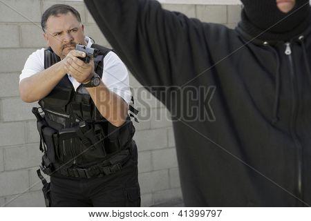 Caucasian police officer aiming gun at thief