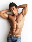 stock photo of physique  - Portrait of a well built shirtless muscular male model against white background - JPG