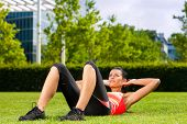 Urban sports - young woman is doing warming up and sit-ups before running in the city