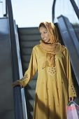 stock photo of dupatta  - Happy Indian woman standing on the escalator with shopping bags - JPG