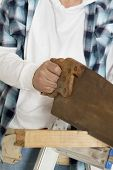 Midsection of male construction worker cutting wood with handsaw