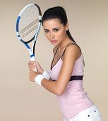 Attractive woman in sportswear playing tennis holding her racquet in both hands ready to play a back