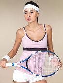 Attractive woman dressed in a tennis outfit and headband holding a tennis racquet in her hands isola