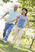 Постер, плакат: Пары работает на открытом воздухе в парке озеро улыбается