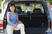 picture of asian woman  - Couples sat in the boot of a car - JPG