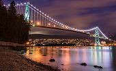 stock photo of gate  - Vancouvers Lions Gate Bridge At Night with beautiful reflection - JPG