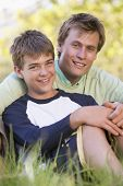 foto of portrait middle-aged man  - Portrait of man and son relaxing in park - JPG