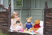 stock photo of tea party  - Young girl having tea party with stuffed toys in home garden - JPG