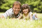 stock photo of father daughter  - Portrait of daughter putting daisy chain on mans head - JPG