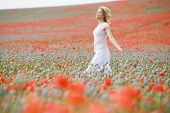 Woman Walking In Poppy Field Smiling