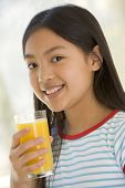 Young Girl Indoors Drinking Orange Juice Smiling