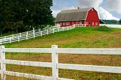 image of red barn  - A white fence leading up to a big red barn - JPG