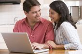 Couples In Kitchen Using Laptop And Smiling