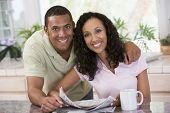 image of current affairs  - Couples smiling at camera with a newspaper and mug infront of them - JPG