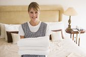 foto of maids  - Female maid cleaning hotel room with towels in hand - JPG