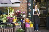 image of flower shop  - Woman florist stoof outside shop - JPG