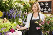 stock photo of flower shop  - Woman florist wrapping bunch of flowers - JPG