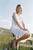 Woman Sitting On Fence Outdoors Smiling