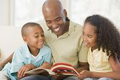 stock photo of father child  - Man reading book with children at home smiling - JPG