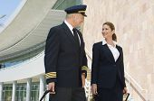 foto of cabin crew  - Happy cabin crew members looking at each other with airport building in the background - JPG