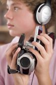 foto of gizmo  - Teenage boy with electronic gadgets in hand and mouth at home - JPG