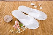 foto of spanking  - Spa or hotel flip flops on a bamboo mat - JPG