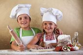 Happy kids with chef hats making pizza toghehter - stretching the dough
