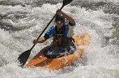 Young Caucasian man kayaking in river