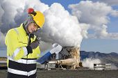 Geothermal engineer and geologist reading data from a list at a gothermal power plant in Iceland, cr