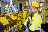 stock photo of levers  - Mechanical engineer posing in the engine room of an offshore supply vessel - JPG