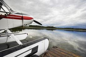 stock photo of float-plane  - Float plane tied up to wooden dock at lake - JPG