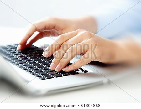 Hands of business woman with laptop computer keyboard.
