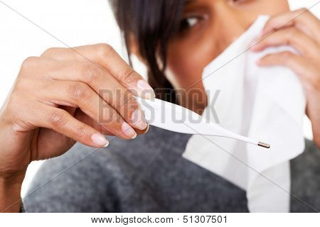 Young sick woman checking her temperature , isolated