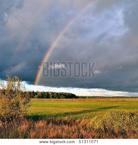 Natural Rainbow Over Autumn Field And Dark Sky.