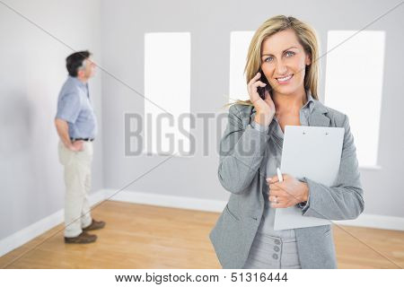 Happy realtor calling someone with her mobile phone in empty house with potential buyer smiling at camera