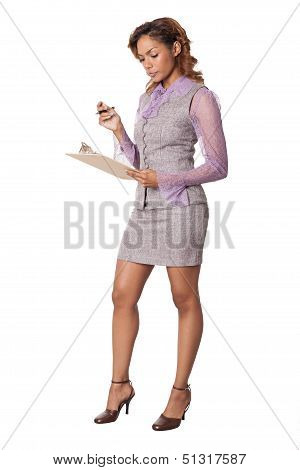 Attractive Business Woman Examines Notes On A Clipboard.