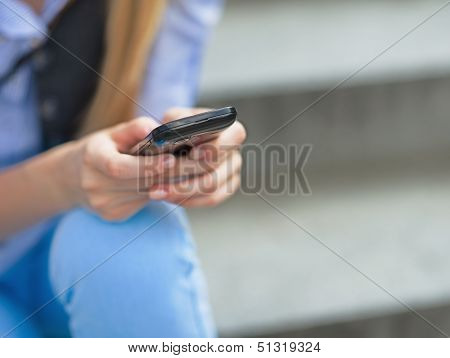 Closeup On Hipster Girl Writing Sms While Sitting On Stairs