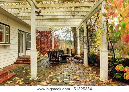 White Farm American House During Fall With Green Grass. Covered Porch.