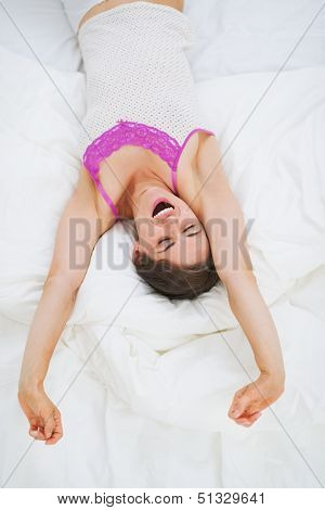 Young Woman Stretching In Bed After Sleep